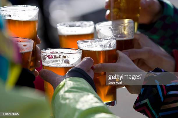 Close up view of a group of friends, raising their pints of beer in a toast on a sunny day on the mountain during a day of skiing.