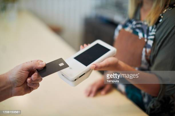 close up view of a hand holding a card near a card reader. - contactless payment stock pictures, royalty-free photos & images