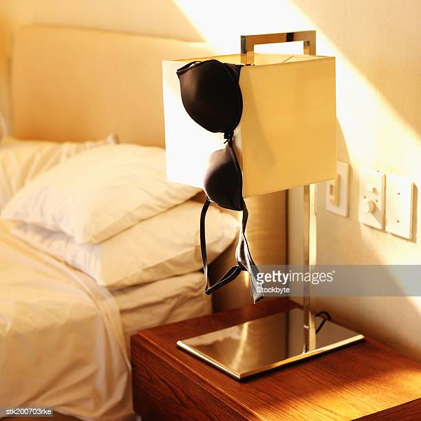 close up view of a lamp with a bra hanging off of it in a bedroom - clothes on clothes off photos stock pictures, royalty-free photos & images