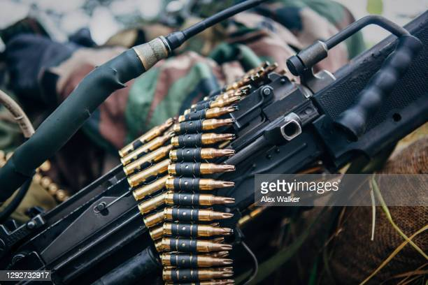 close up view of a light machine gun with black training rounds resting on top and a soldier in background - gunman stock pictures, royalty-free photos & images