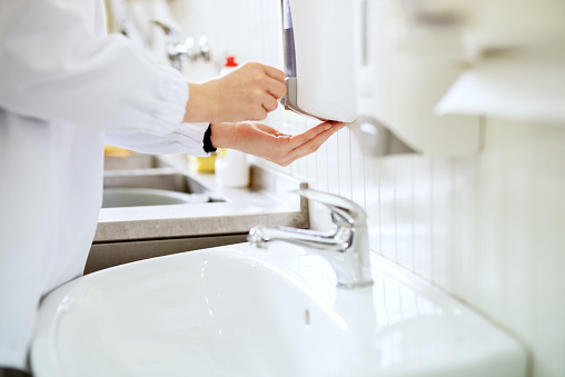 Close up view of a worker in sterile cloths washing hands a bathroom before working. 943535564