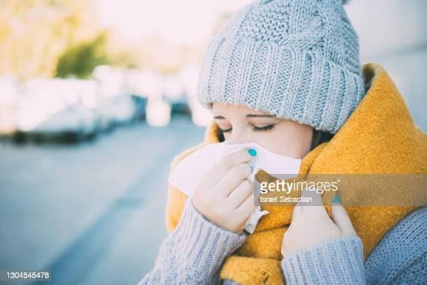 close up view of a young caucasian woman dressed in winter clothing as she blows her nose from being ill. - mucus stock pictures, royalty-free photos & images