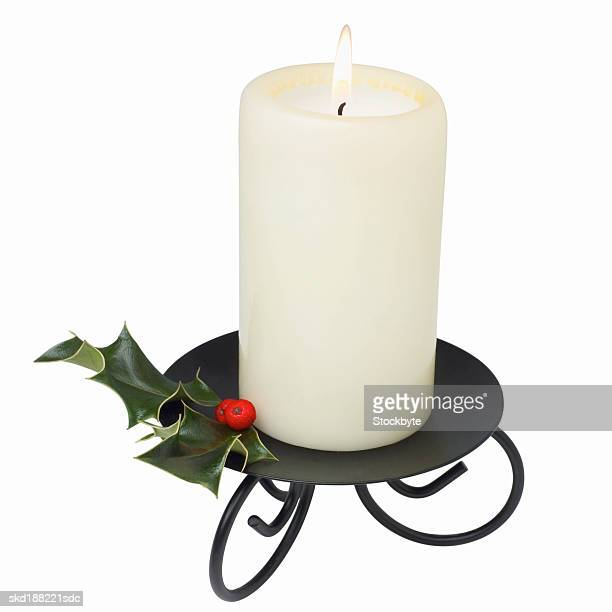 Close up view of Christmas candle and a piece of holly