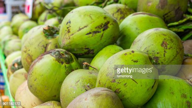 close up view of coconuts for sell by the street - coconut water stock pictures, royalty-free photos & images