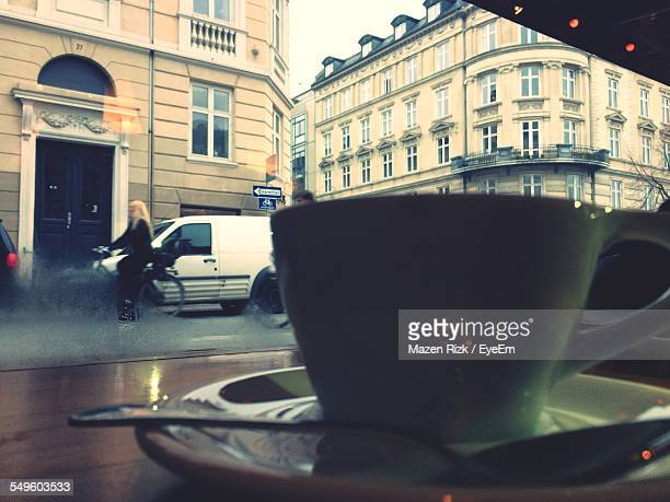 close up view of coffee cup on cafe table with city street in background - livello di superficie foto e immagini stock