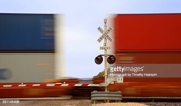 close up view of colorful train cars speeding through an intersection - timothy hearsum stock-fotos und bilder