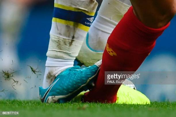 A close up view of Everton's English midfielder Ross Barkley's boot catching Liverpool's Croatian defender Dejan Lovren Barkley was subsequently...