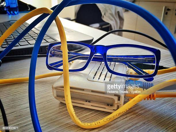 Close Up View Of Eyeglasses Among Yellow And Blue Modem Cables