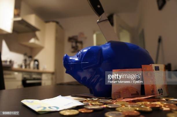 Close Up View Of Money By Piggy Bank On Table At Home