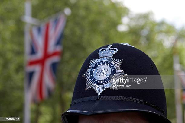 A close up view of the helmet of a Metropolitan Police policeman standing in The Mall with a Union Jack flag in the background.