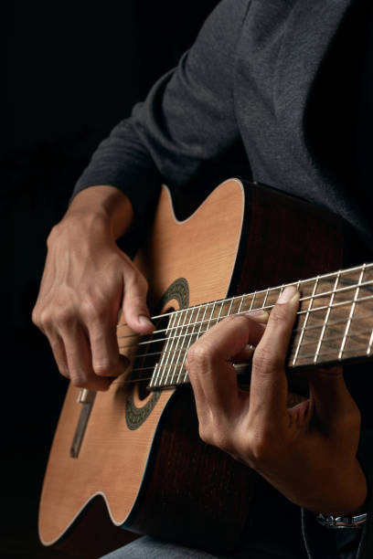 Close up view of the musician's hand is playing the acoustic guitar on a dark background