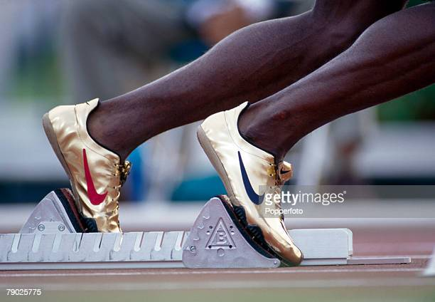 Close up view of the Nike gold running shoes of American track athlete Michael Johnson competing during the heats before finishing in first place in...