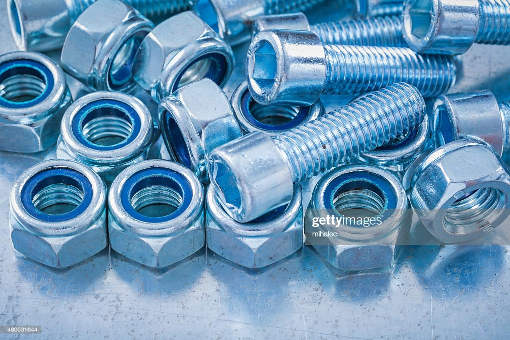 Close up view of threaded construction nuts and screw bolts : Stock Photo