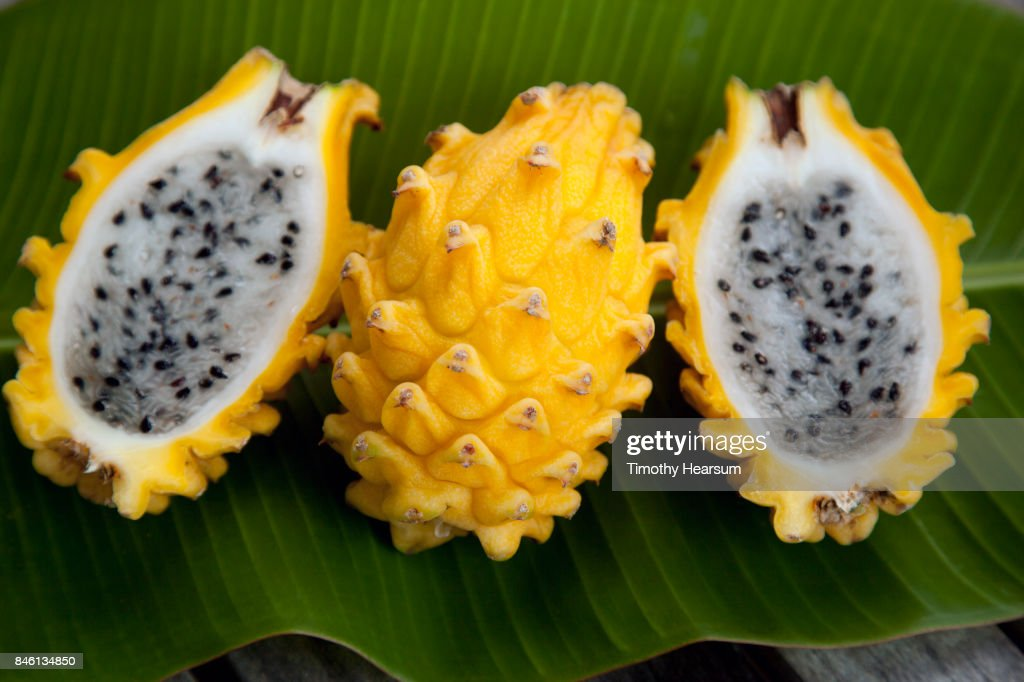 Close up view of whole dragonfruit and dragonfruit halves on a banana leaf : Stock Photo