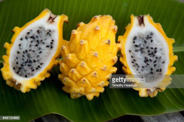 close up view of whole dragonfruit and dragonfruit halves on a banana leaf - パホア ストックフォトと画像