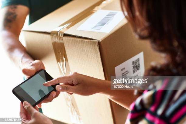 close up view of woman signing on smartphone for delivery - writing stock pictures, royalty-free photos & images