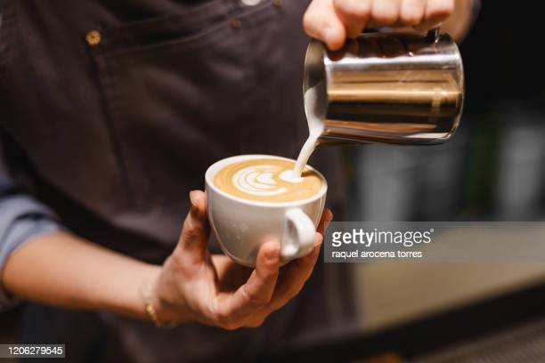 close up view of young woman preparing a coffee by drawing a flower with milk - serving food and drinks stock pictures, royalty-free photos & images