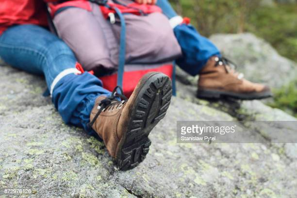 close up view on hikers boots and backpack on rock - 靴底 ストックフォトと画像