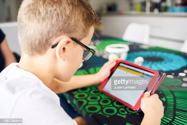 close up view over the shoulder of boy looking at a digital tablet - utilizar o tablet - fotografias e filmes do acervo