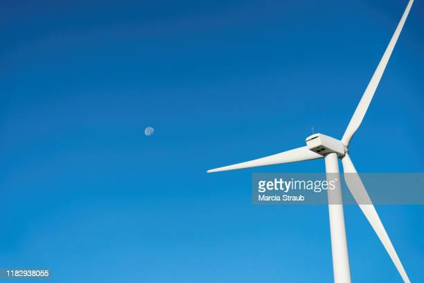 close up wind turbine and moon on a clear morning - amerikanische farm windmühle stock-fotos und bilder