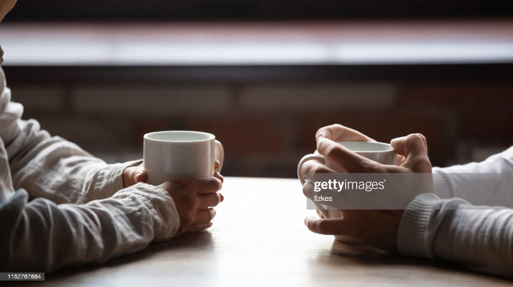Close up woman and man holding cups of coffee on table : Stock Photo