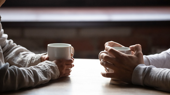 Close up woman and man holding cups of coffee on table 1152767884
