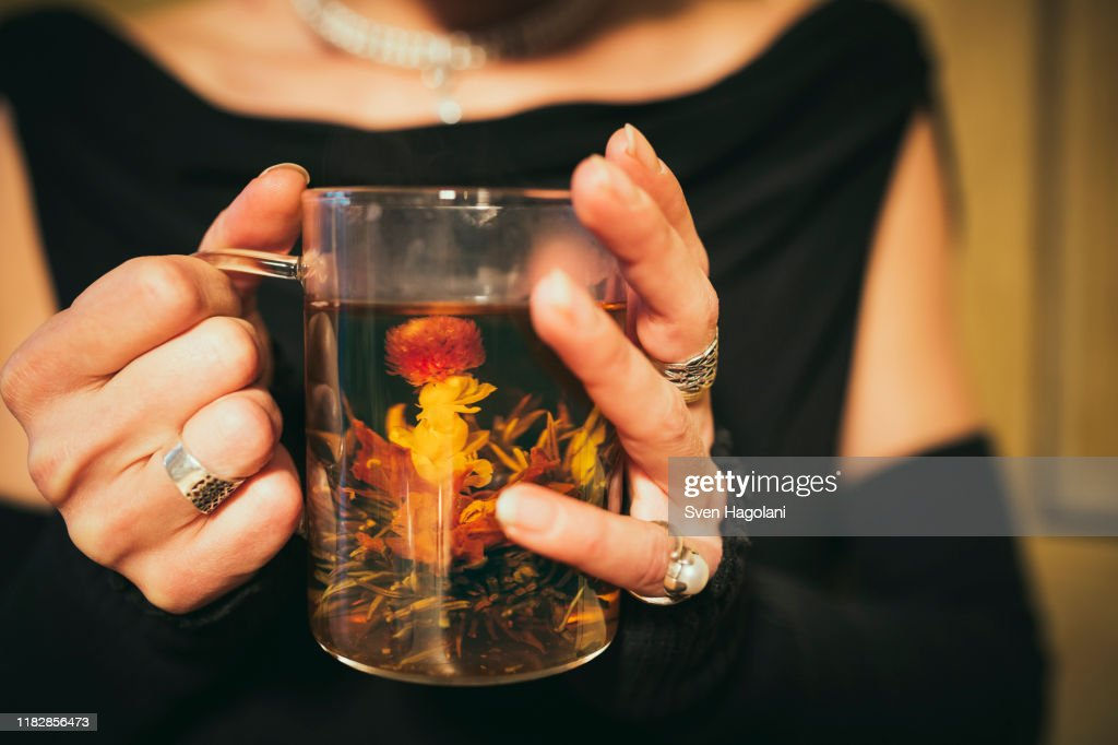 Close up woman drinking blooming tea : Stock Photo