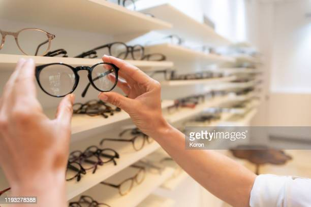 close up woman hands selecting eyeglasses in optical store - めがね類 ストックフォトと画像
