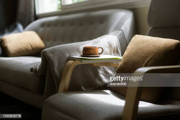 close up wooden coffee cup on cozy sofa bed - cosy stock pictures, royalty-free photos & images