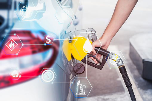 close up worker hand holding nozzle fuel for fill oil into car tank at pump gas and oil station with technology icons concept design - gettyimageskorea