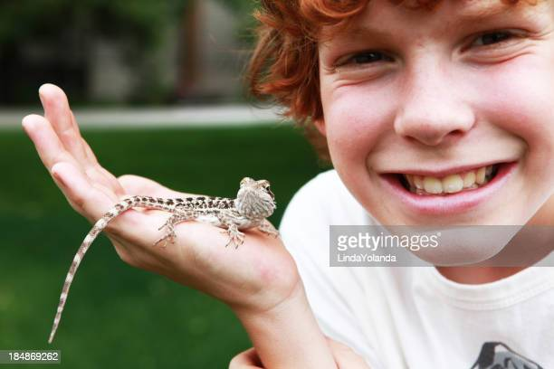 Close up Young boy in garden, smiling, holding small lizard