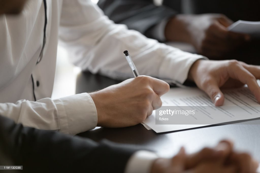 Close up young male manager hands signing contract. : Stock Photo