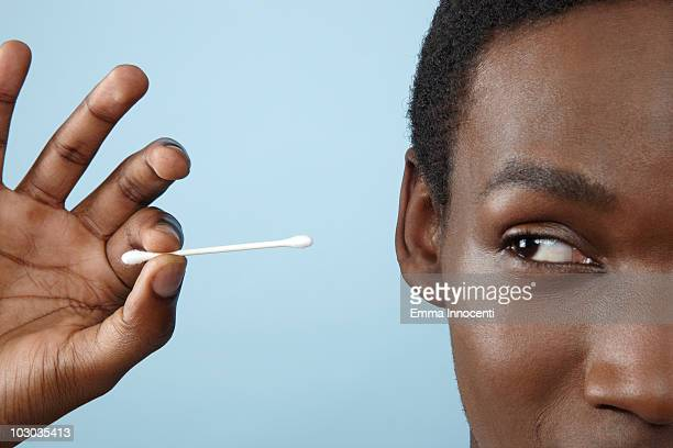 close up young man holding cotton bud