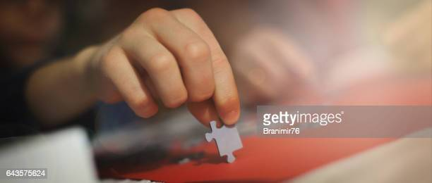 Close up-boy is playing with puzzles