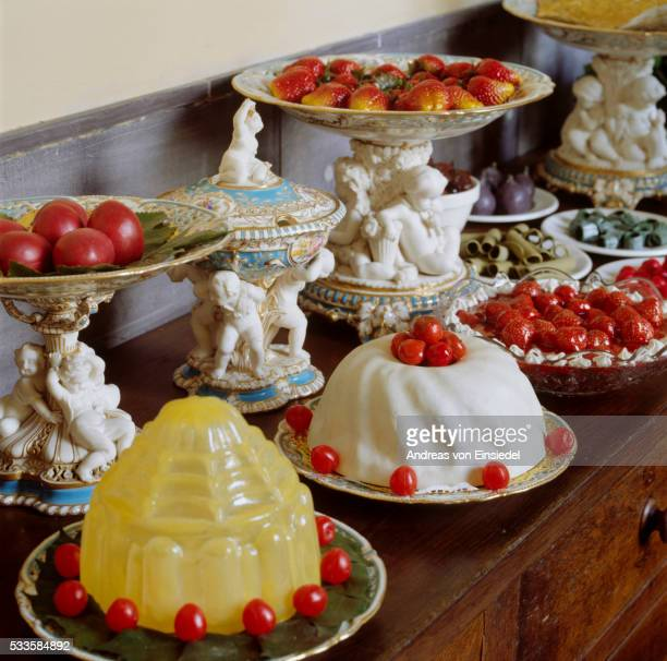 Close view of a table loaded with fruit & desserts on Minton dessert service, and cake stands, 1850s