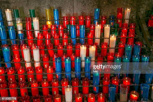Close view of the collection of lit prayer candles inside the church