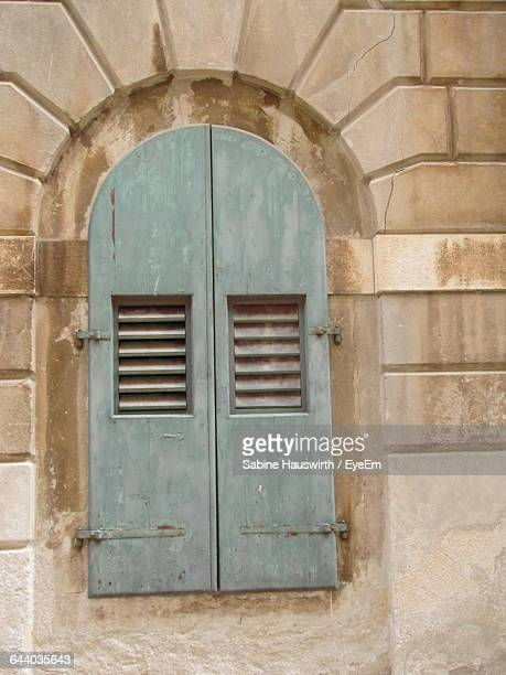 closed arch window of weathered building - sabine hauswirth stock pictures, royalty-free photos & images
