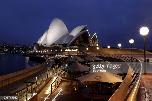 Closed bars and restaurants along the Sydney Opera House forecourt at Circular Quay during a lockdown imposed due to the coronavirus, at night in...