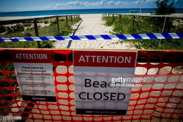 A closed beach signage is seen at Coolangatta Beach on the Queensland New South Wales border in Brisbane on April 15 2020 A state border that bisects...