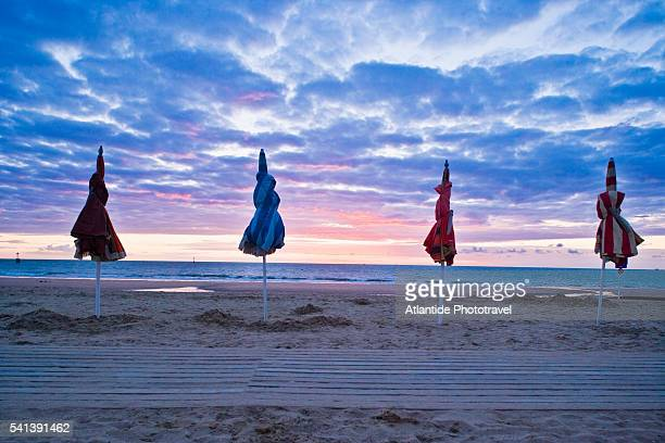 closed beach umbrellas at sunset - trouville sur mer stock pictures, royalty-free photos & images