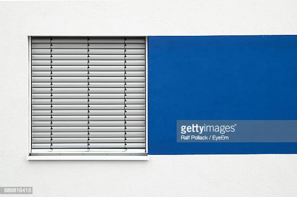 Closed Blinds Window Next To Blue Painted Square Shape