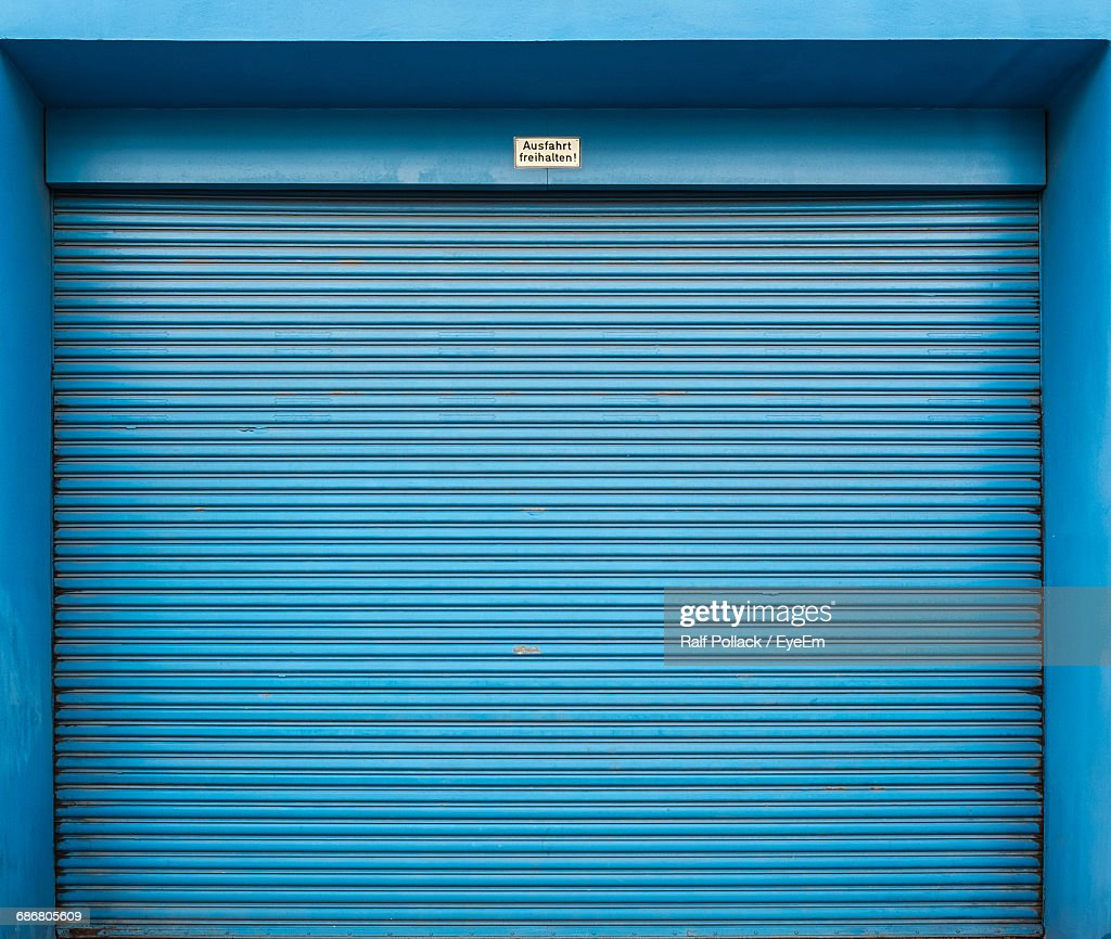 Closed Blue Shutter Of Store : Stock Photo