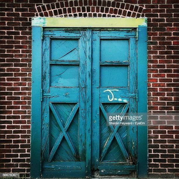 closed blue wooden door against brick wall of house - letra j - fotografias e filmes do acervo