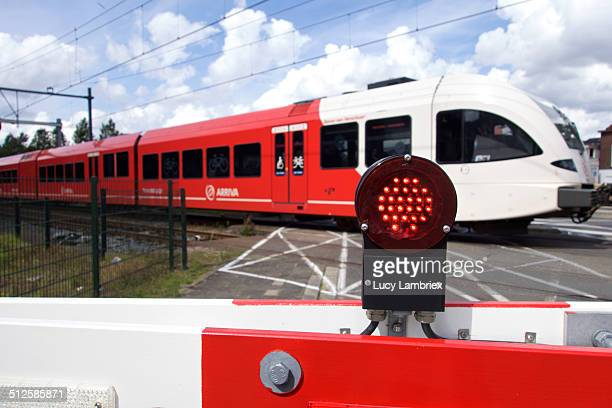 Closed boom barrier with red light and Arriva train passing by Dordrecht Netherlands