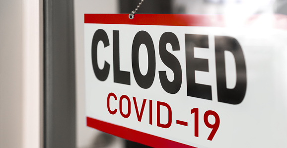 Closed businesses for COVID-19 pandemic outbreak, closure sign on retail store window banner background. Government shutdown of restaurants, shopping stores, non essential services 1220230580