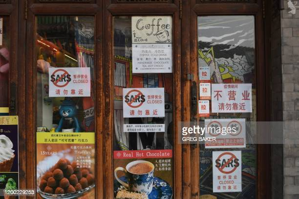 """Closed cafe displays """"SARS Closed"""" signs on its door in an alley in Beijing on February 12, 2020. - The death toll from the COVID-19 coronavirus..."""