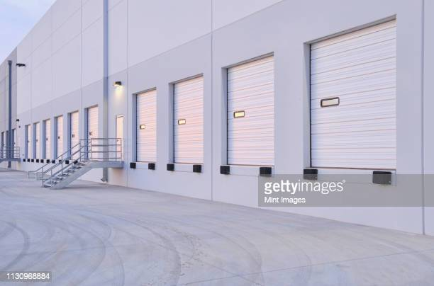 closed doors of warehouse loading dock - roller shutter stock pictures, royalty-free photos & images