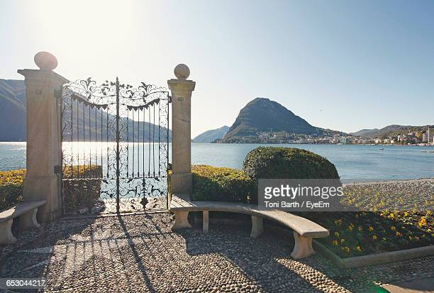 Closed Gate By Lake And Mountains Against Clear Sky