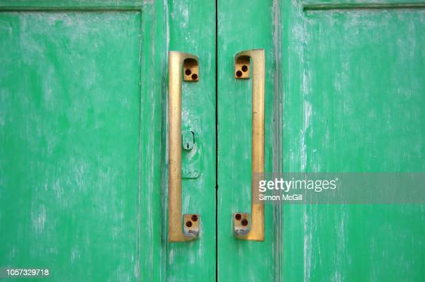Closed green-painted wooden double doors with brass handles