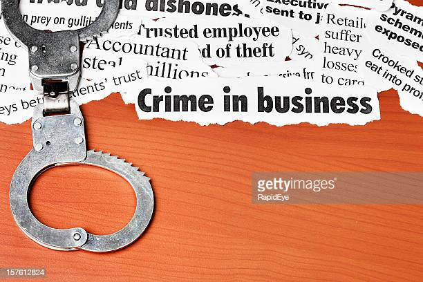 Closed handcuffs rest on white collar crime headlines